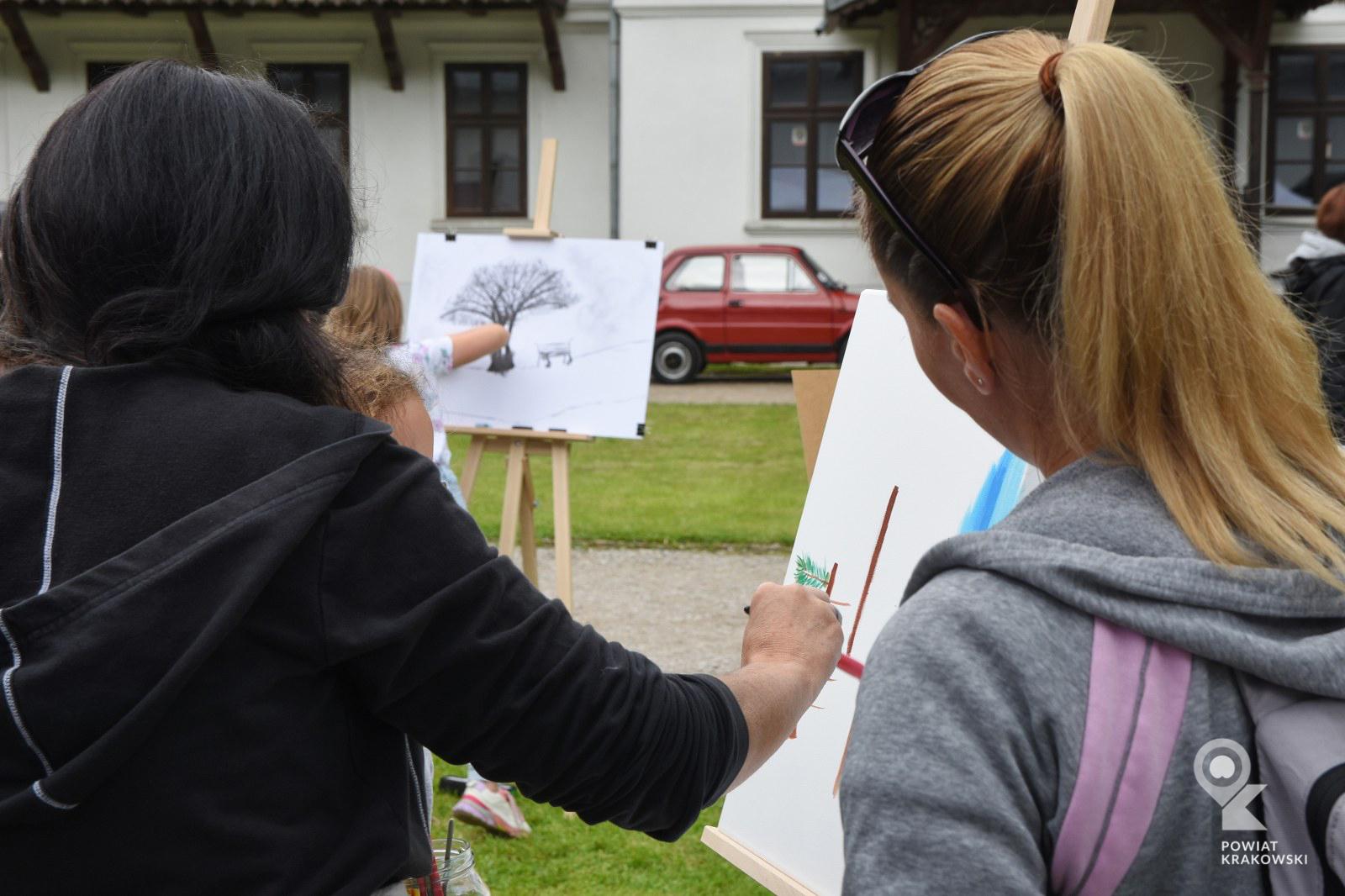 Kobieta maluje obrazek, druga kobieta się przygląda. W tle dziecko rysuje drzewo