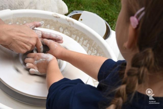 Dziewczynka przy kole garncarskim trzyma dłonie w kręcącej się glinie, dwie dodatkowe dłonie pomagają jej