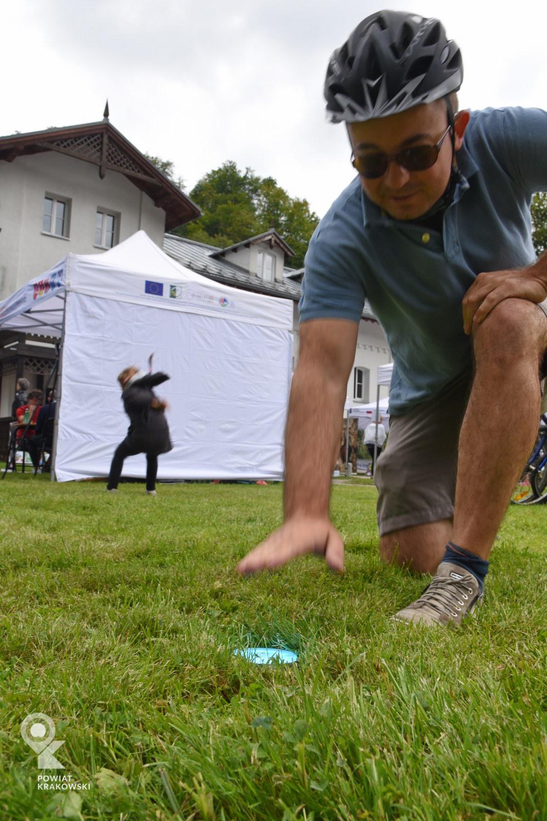 Mężczyzna w kasku rowerowym uderza w krążek leżący na trawie