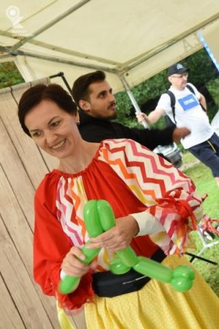 Uśmiechnięta kobieta skręca zwierzątko z balona
