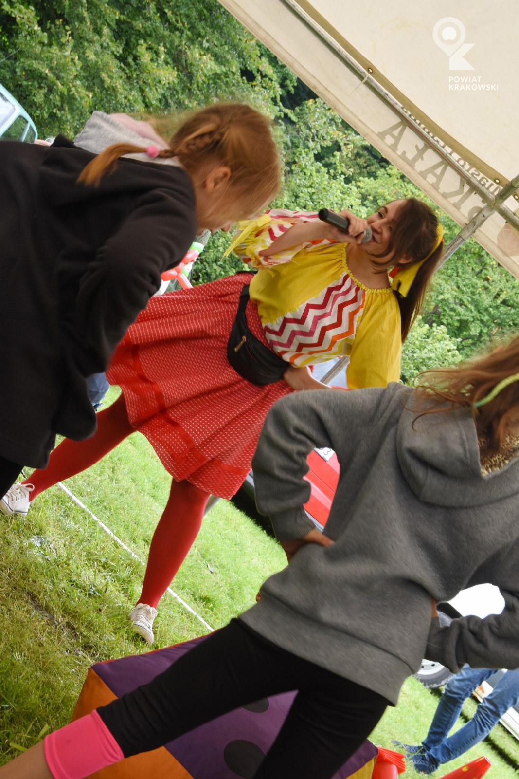 Kobieta z mikrofonem stoi na szeroko rozstawionych nogach, przed nią zwrócone do niej twarzami dwie dziewczynki