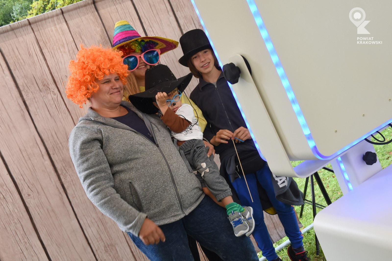 Dwóch dorosłych i dwoje dzieci w zabawnych okularach, perukach i kapeluszach patrzy w biały prostopadłościan, w którym jest aparat fotograficzny