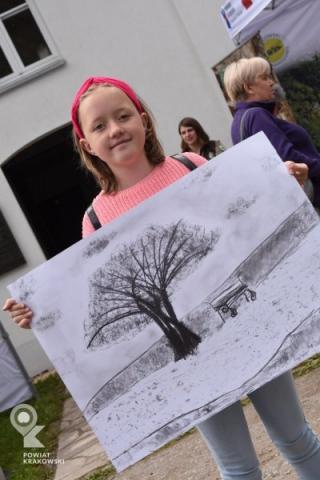 Dziewczynka prezentuje narysowany przez siebie obrazek z drzewem i ławką